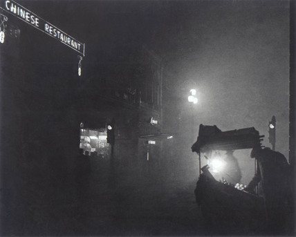 'A foggy Piccadilly partially lit by the light from a fruit seller's stall', 1952.