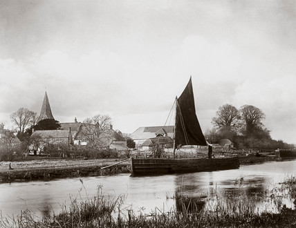 Sailing boat moored by a village, c 1890s.
