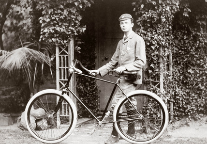 C S Rolls standing with a bicycle, c 1895.