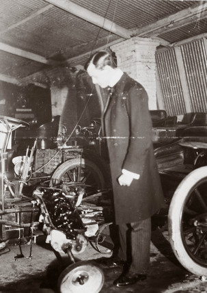 C S Rolls looking at the engine of a motor car in his garage, c 1900.
