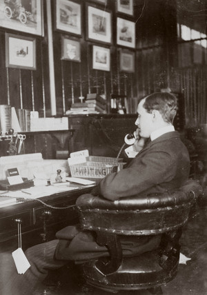 C S Rolls sitting at his desk talking on the telephone, c 1900.