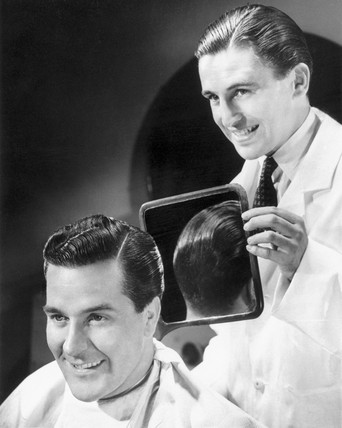 Man inspecting the back of his new haircut in a barber's mirror, c 1940s.