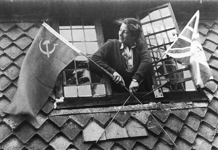 Woman with Union Jack and Soviet flags on VE Day, 8 May 1945.