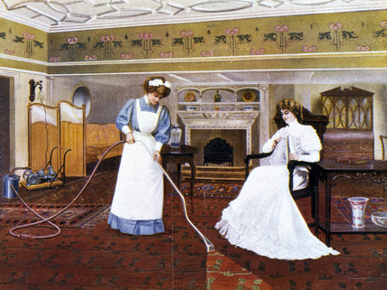 Maid vacuuming whilst seated lady looks on, 1911.