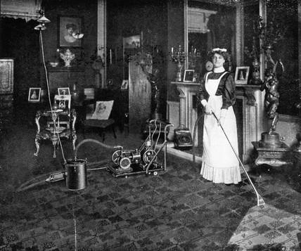Maid vacuuming carpet, 1911.