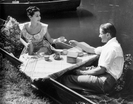 Couple having tea by a riverbank, 1940s.