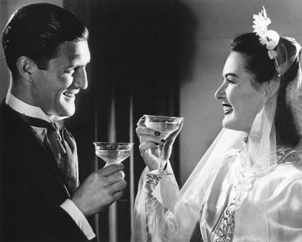 Newlyweds enjoying a glass of champagne, 1940s.