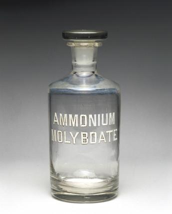 Clear glas reagent bottle labelled 'AMMONIUM MOLYBDATE', 1930.