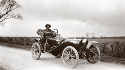 Woman driving a motor car, c 1912.
