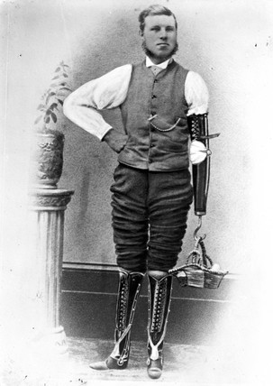 Man wearing two artificial legs and an artificial arm, c 1906.