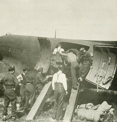 Unloading a jeep from a Fedden Mision's Dakota aircraft, June 1945.