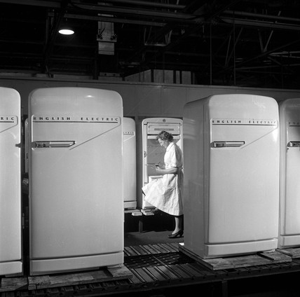 A female production line worker inspects refrigerators, 1954.