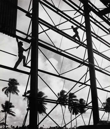Builders balance on girders of new sugar factory, Guyana, 1958.