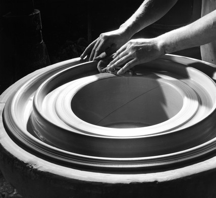 A potter's hands shaping a ceramic core used in electrical power distribution.