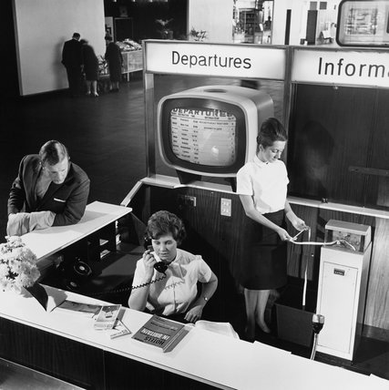Information desk at Manchester Airport including woman with ticker tape, 1965.