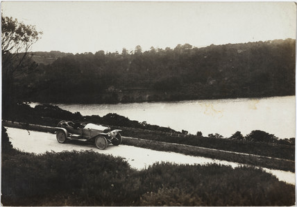 Motor car alongside a river, c 1912.