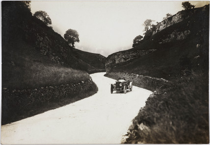 Motor car on a winding road, c 1912.