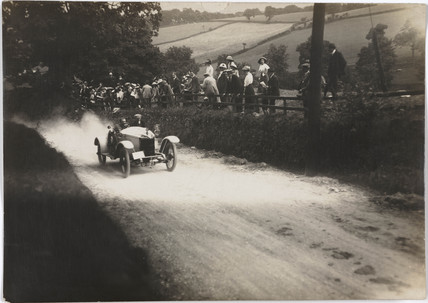 Motor car driving uphill on a country road, c 1912