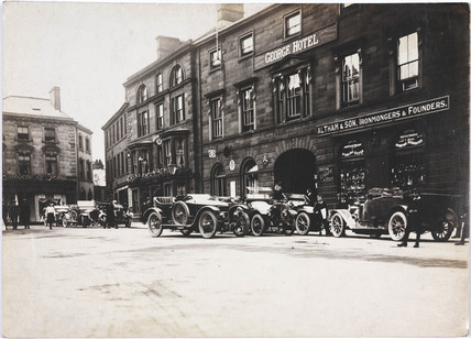 Motor cars parked outside a hotel, c 1912.