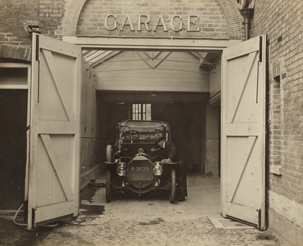 Motor car in a garage, c 1910s.