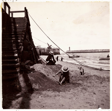 People digging in the sand, Whitby, c 1905.