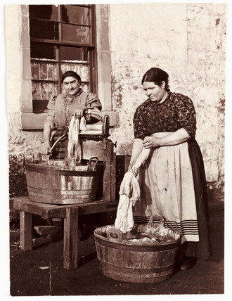 Two women washing clothes, c 1905.