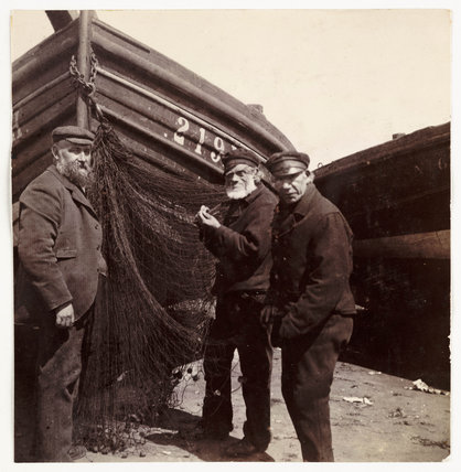 Fishermen standing by a net, c 1905.