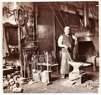 Blacksmith in a foundry, c 1905.