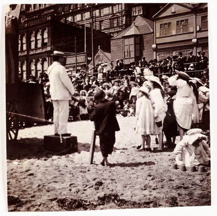 Crowd watching a beach entertainer, c 1905.