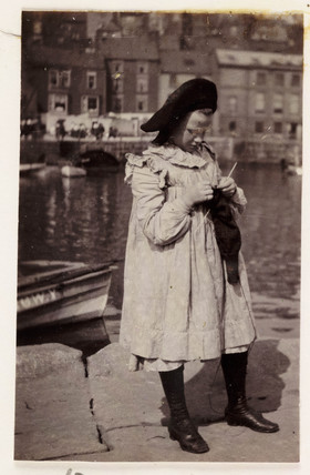 Girl knitting, c 1905.