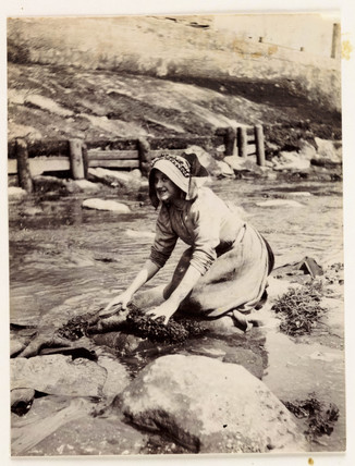 Woman scrubbing by the water's edge, c 1905.