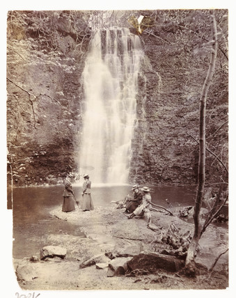 Women at the foot of a waterfall, c 1905.