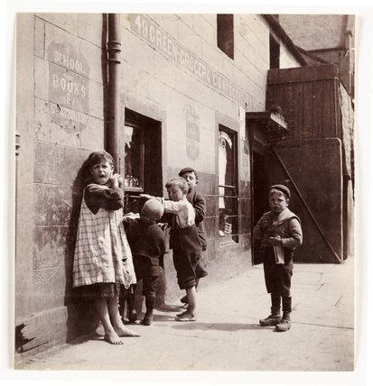 A group of children outside a greengrocer's shop, c 1905.