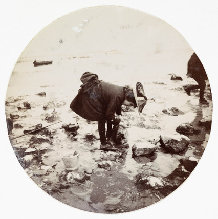 Girl looking in a rock pool, c 1890.