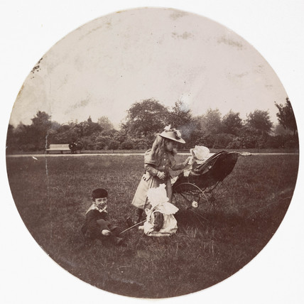 Three children with a baby in a pram, c 1890.