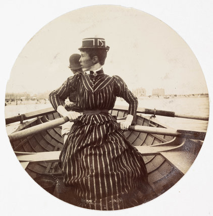 Woman in a rowing boat, c 1890.
