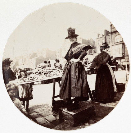 Woman at a market stall, c 1890.