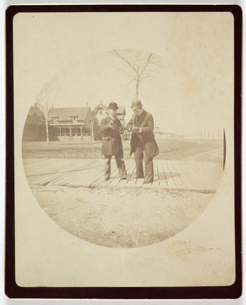 Two men on a boardwalk, c 1890.