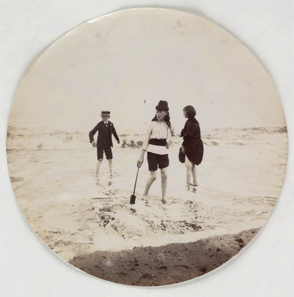 Two girls and a boy paddling in the sea, c 1890s.