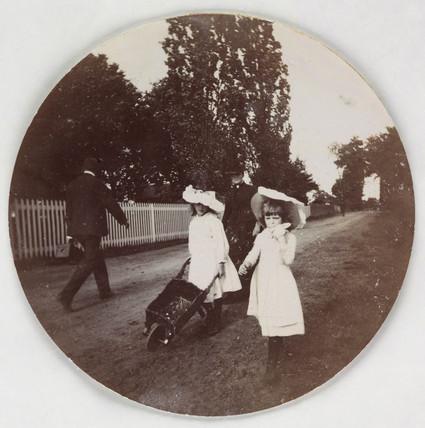 Children walking with a wheelbarrow, c 1890.