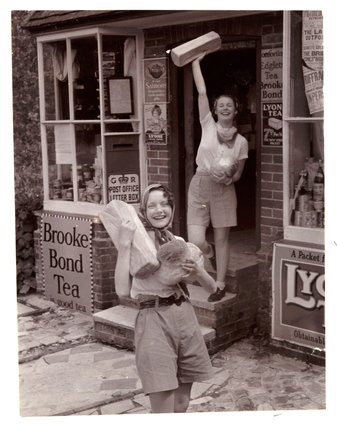 Two women carrying loaves of bread, c 1935.