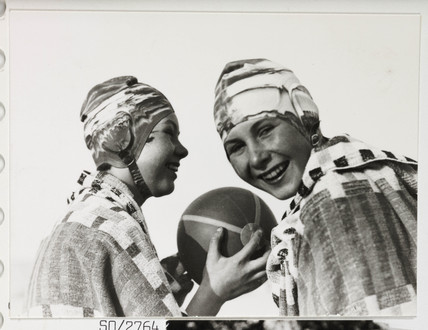 Two girls in swimming caps, c 1930.