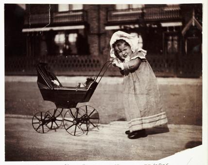 Child pushing a toy pram, c 1895.