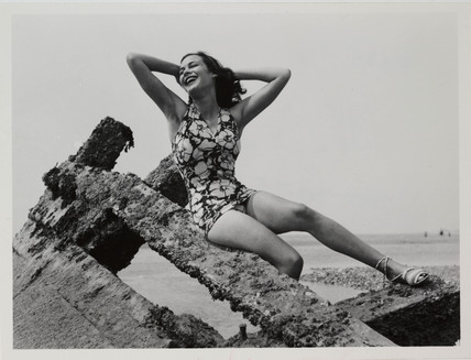 Woman posing in swimsuit on a breakwater, c 1940.