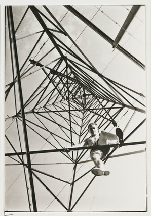 Man climbing a pylon, c 1930.