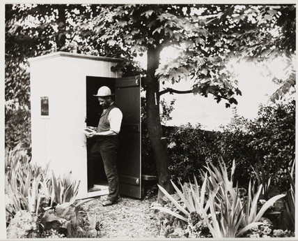 Man inspecting a photographic plate outside his darkroom, c 1900s.
