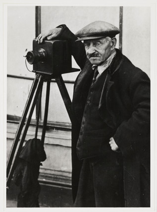 Photographer standing beside his tripod-mounted plate camera, c 1890s.