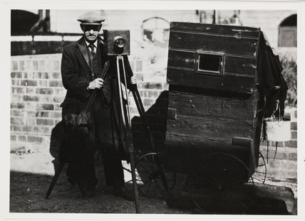 Photographer with tripod-mounted plate camera and other equipment, c 1890s.
