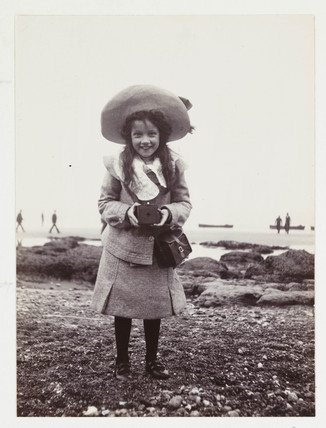 Kodak Brownie girl on beach holding a Kodak Brownie camera, c 1900.