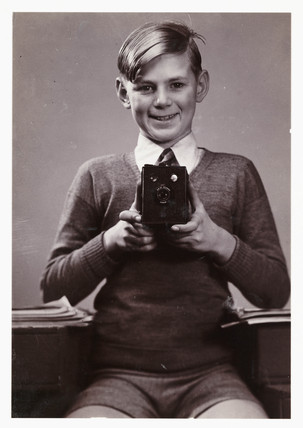 Boy with box camera, c 1930s.